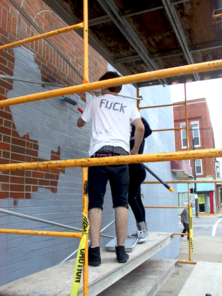 students painting from the scaffold